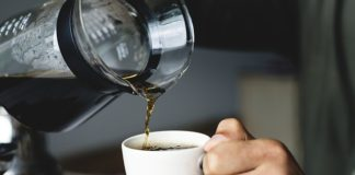 pouring brewed coffee in a white cup