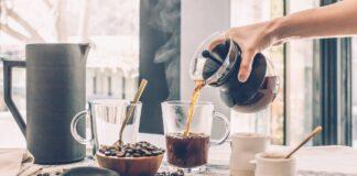 A person putting black coffee into a mug