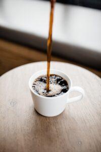pouring coffee in a white ceramic mug