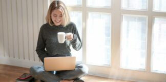 a woman drinking coffee and using laptop