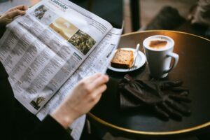 a person reading newspaper with coffee on the table