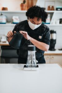a barista pouring hot water