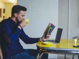 a person reading a book and drinking coffee