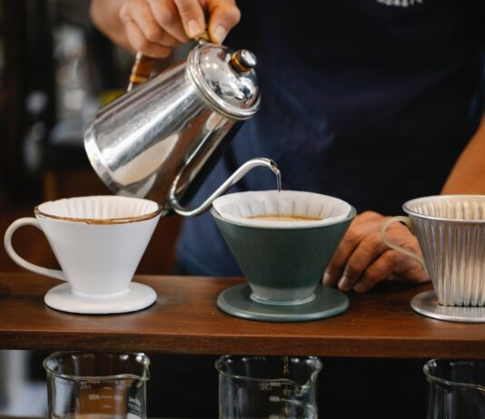 A person pouring coffee into cups
