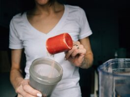 a woman adding a scoop of protein powder